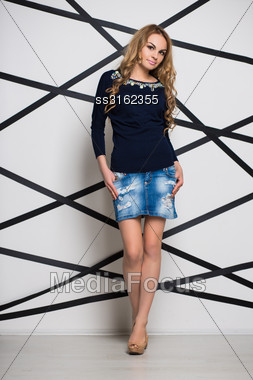 Pretty Blond Woman Posing In Blue Jeans Skirt And Blouse Stock Photo