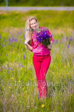 Pretty Blond Woman Posing In The Field With Flowers Stock Photo