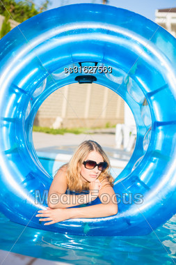 Pretty Blond Woman Posing With Rubber Ring In Swimming Pool Stock Photo