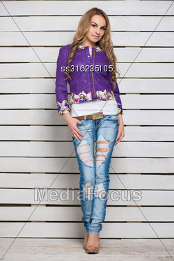 Pretty Blond Woman In Ripped Jeans And Purple Jacket Posing Near The White Wooden Wall Stock Photo