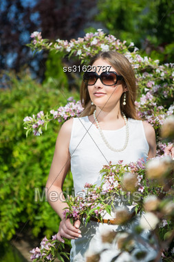 Pretty Blond Woman In Sunglasses Posing Near Blooming Tree Stock Photo