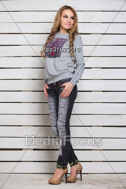 Pretty Blond Woman Wearing Gray Hoody And Black Jeans Posing Near White Wooden Wall Stock Photo