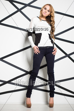 Pretty Blond Woman Wearing Jeans And White Blouse Posing In The Studio Stock Photo