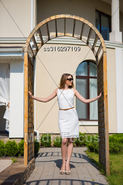 Pretty Blond Woman Wearing White Dress And Sunglasses Posing In Archway Stock Photo