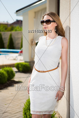 Pretty Blond Woman Wearing White Dress And Sunglasses Posing Outdoors Stock Photo