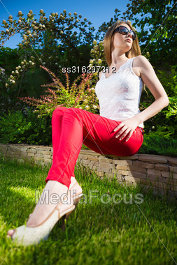 Pretty Blond Woman Wearing White Top And Red Panties Sitting On The Stone Fence Stock Photo