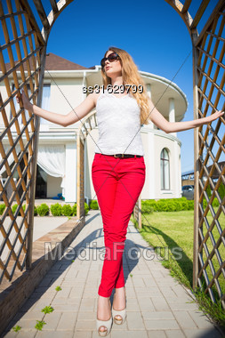 Pretty Blond Woman Wearing White Top And Red Panties Posing In Archway Outdoors Stock Photo