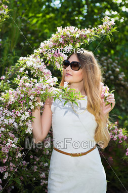 Pretty Blond Woman In White Dress Posing Near Blooming Tree Stock Photo