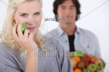 Pretty Blonde With Apple And Man Holding Basket In Background Stock Photo
