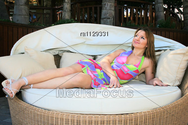 Pretty Blonde Girl Lying On Outdoor Sofa Stock Photo