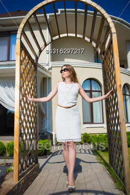 Pretty Blonde Wearing White Dress And Sunglasses Posing In Archway Stock Photo