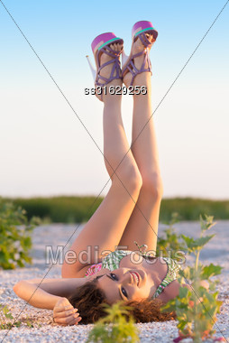 Pretty Brunette Lying On The Ground And Showing Her Beautiful Long Legs Stock Photo