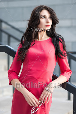 Pretty Brunette In Red Dress Posing Near The Railing Stock Photo