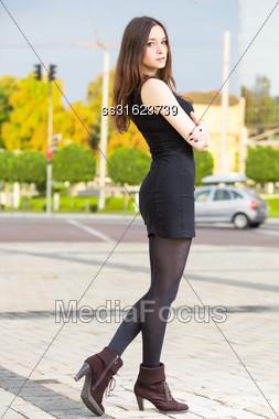 Pretty Brunette Wearing Black Dress Posing Outdoors Stock Photo