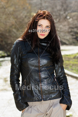 Pretty Brunette Wearing Black Jacket And Keeping Hands In Her Pockets Stock Photo