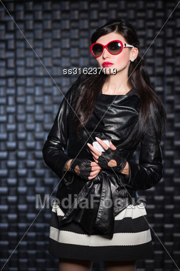Pretty Brunette Wearing Black Jacket And Red Sunglasses Posing With A Mobile Phone Stock Photo
