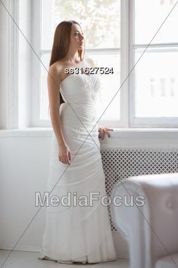 Pretty Brunette In White Wedding Dress Posing Near The Window Stock Photo