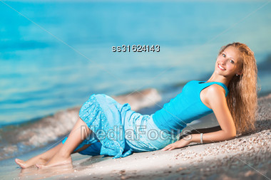 Pretty Cheerful Blond Woman Lying On The Beach Stock Photo