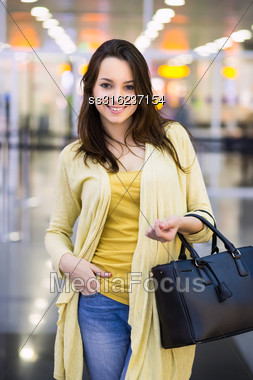Pretty Cheerful Woman Wearing Yellow Blouse Posing In The Airport Terminal Stock Photo