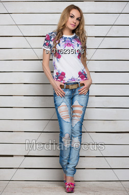 Pretty Curly Blond Woman Posing In Blue Ripped Jeans And White Flowered T-shirt Stock Photo