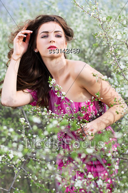 Pretty Curly Brunette Wearing Pink Dress And Posing In Blooming Garden Stock Photo