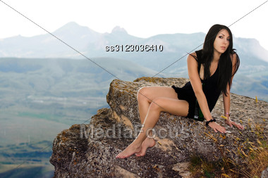 Pretty Girl With A Champagne Bottle Sits On A Rock Stock Photo