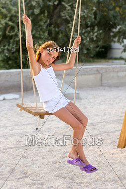 Pretty Little Girl Swinging On A Swing Outdoors Stock Photo