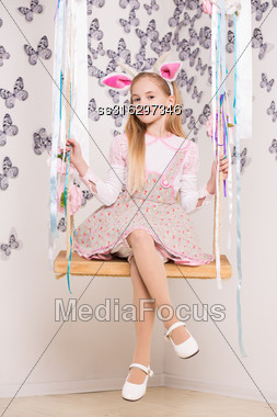 Pretty Little Girl Wearing Goat Costume Posing On The Swing Stock Photo
