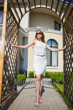Pretty Slim Blond Woman Posing In Archway Outdoors Stock Photo