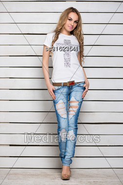 Pretty Slim Blonde In Jeans And T-shirt Posing Near The White Wooden Wall Stock Photo