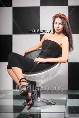 Pretty Slim Brunette Posing On A Chair In The Studio Stock Photo
