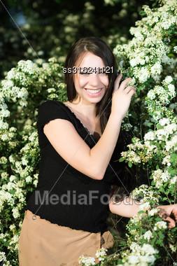 Pretty Smiling Brunette Posing Near The Flowering Bush Stock Photo