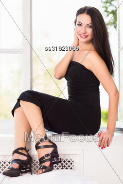 Pretty Smiling Brunette Sitting On The Windowsill Stock Photo