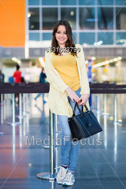 Pretty Smiling Woman With Black Bag Posing In The Airport Terminal Stock Photo
