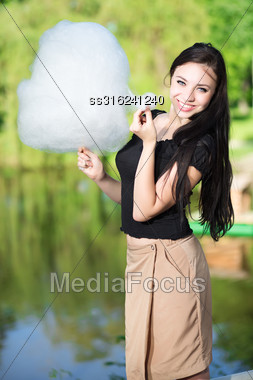 Pretty Smiling Woman Posing With A Cotton Candy Near The Pond Stock Photo