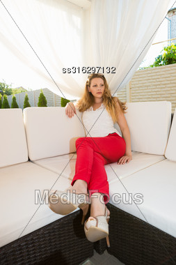 Pretty Thoughtful Blond Woman Relaxing In Summer House Stock Photo