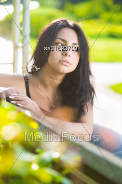Pretty Thoughtful Brunette Posing On The Bench Stock Photo