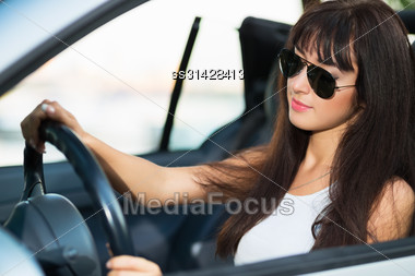 Pretty Thoughtful Brunette Wearing Sunglasses Posing In Grey Car Stock Photo
