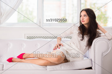 Pretty Thoughtful Lady Posing On The Sofa Stock Photo