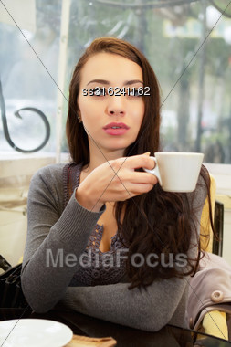Pretty Thoughtful Woman Drinking In A Cozy Cafe Stock Photo