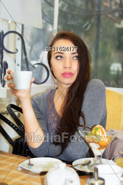Pretty Thoughtful Woman Sitting In The Restaurant And Holding A Cup Stock Photo