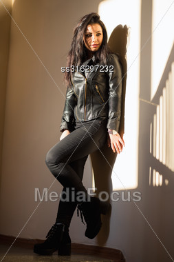 Pretty Woman In Black Clothes Posing Near The Wall Stock Photo