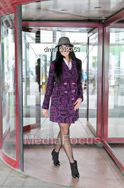 Pretty Woman In A Coat Going Thru Revolving Doors Stock Photo