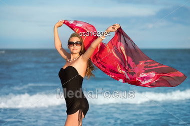 Pretty Woman With Flowered Pareo Posing On The Beach Stock Photo