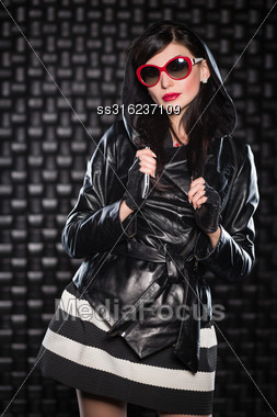 Pretty Woman Wearing Leather Jacket With A Hood And Red Sunglasses Stock Photo