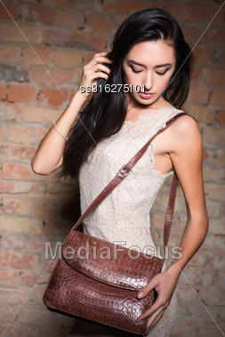 Pretty Woman Wearing White Lace Dress Posing With Handbag Stock Photo