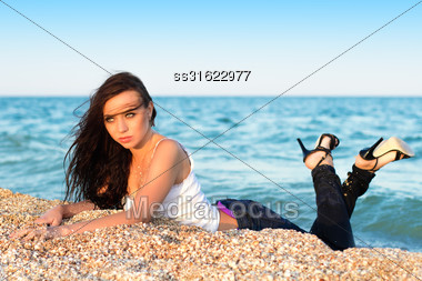 Pretty Woman In White Shirt And Jeans Lying On The Beach Stock Photo