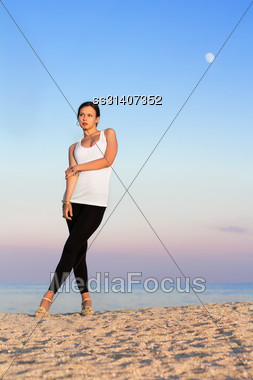 Pretty Woman In White T-shirt And Tight Black Leggings Posing On The Beach Stock Photo