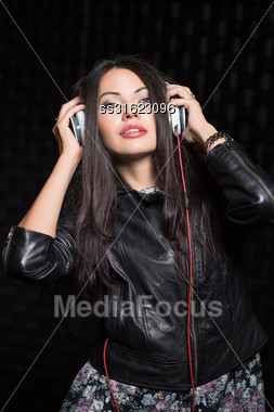 Pretty Young Black-haired Woman Posing With Headphones. Isolated On Black Stock Photo
