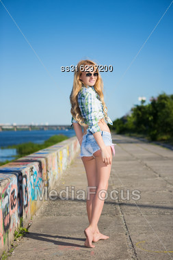 Pretty Young Blond Woman In Jeans Shorts Posing Outdoors Stock Photo